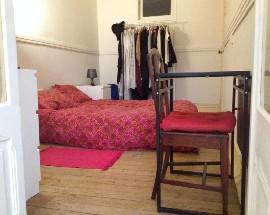 Quarto grande com cama de casal e espaco de refeicoes anexo